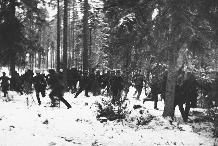 """In a frozen, wooded battlefront """"somewhere in Finland,"""" Finnish troops scatter to take shelter as Soviet planes fly over on an air raid on January 19, 1940."""
