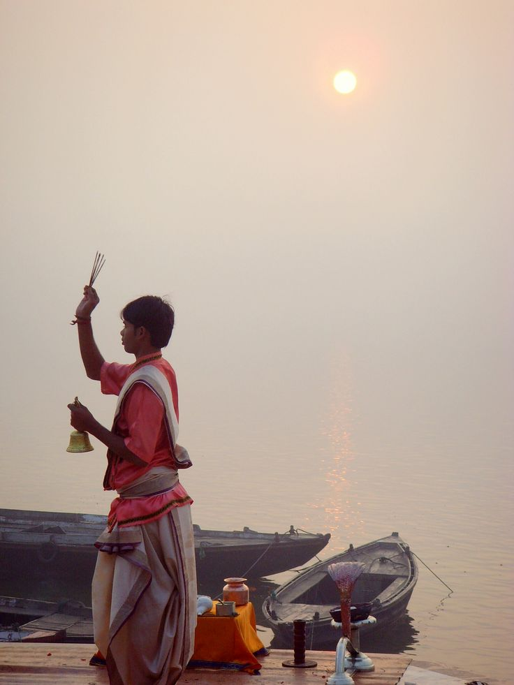 Hindu priest offering prayers to the elements of nature at the banks of the river Ganges - Varanasi, Uttar Pradesh, North India.