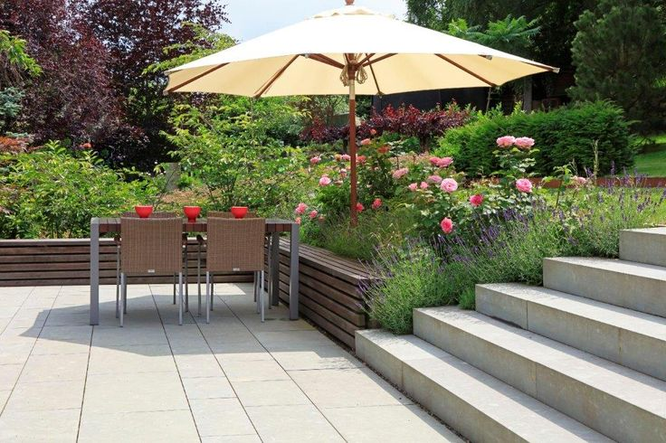 Helle, großformatige Betonsteinplatten und Blockstufen geben dem Auge im üppig bepflanzten Genießer-Garten Ruhe und Balance.