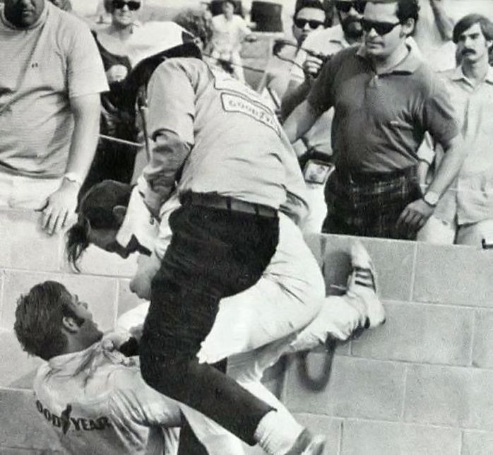 Peter Revson attacks Sam Posey at Riverside Raceway in 1970. Trying to break up the fight is Carroll Smith of the Shelby Team. Pete Biro took the photo. Posey and Revson became good friends after this incident.   Revson apparently had a temper. He threatened a track official at Sebring in 1972 after he was black flagged for passing under the yellow. He was tossed from that race.