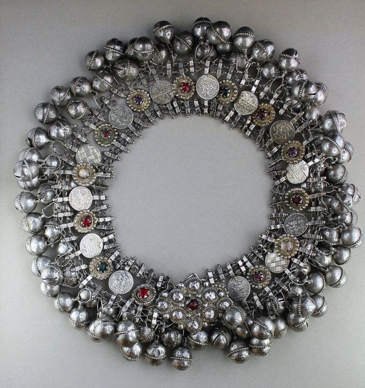 """This is a huge Yemeni belt in high grade silver with mysterious symbols. (See more photos in the comments) Featuring coin pendants strung on silver chains with profuse bells. Each coin shape is marked differently. Some have glass stones: red, purple, blue, green, and clear. Some are castings of a 1912 gold sovereign showing St George slaying the dragon. Some have strange markings including cross-hatches, the roman numerals """"X B V"""" and floral shapes. One coin is marked with David's star."""