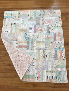 Any new mother and baby will be delighted with this low volume scrappy baby quilt. The backing is a very sweet pink kitten fabric as shown in the last photo. Lined with a cotton batting and quilted with modern straight lines, this quilt is sure to be the perfect addition to any nursery.
