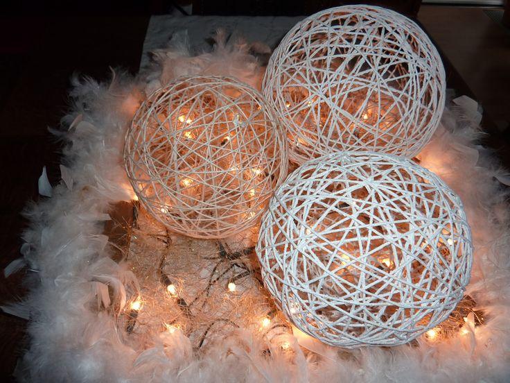 Koordballendeco: drenk koord in verdunde houtlijm en wikkel rondom een ballon. Laat drogen en verwijder dan de ballon. Maak een basis van een houten kader, waarop je kippengaas vasthecht. Een lichtjeskabel op deze basis, enkele koordballen, en een witte boa eromheen: gezellig sfeerlicht!