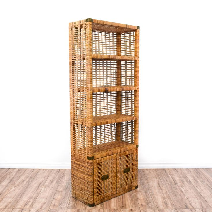 This tropical bookcase is featured in a woven wicker rattan with a warm wood finish. This bohemian bookshelf has 4 shelf tiers, a bottom cabinet and brass campaign style hardware. Perfect for displaying books in a beach chic space! #bohemian #storage #bookcase&shelving #sandiegovintage #vintagefurniture