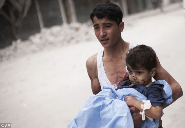 Desperate attempts: A Syrian youth holds a child wounded by Syrian Army shelling near Dar El Shifa hospital in Aleppo, Syria