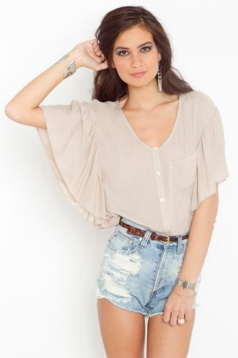 Oversized cream blouse featuring ruffled batwing sleeves and shell button closures.