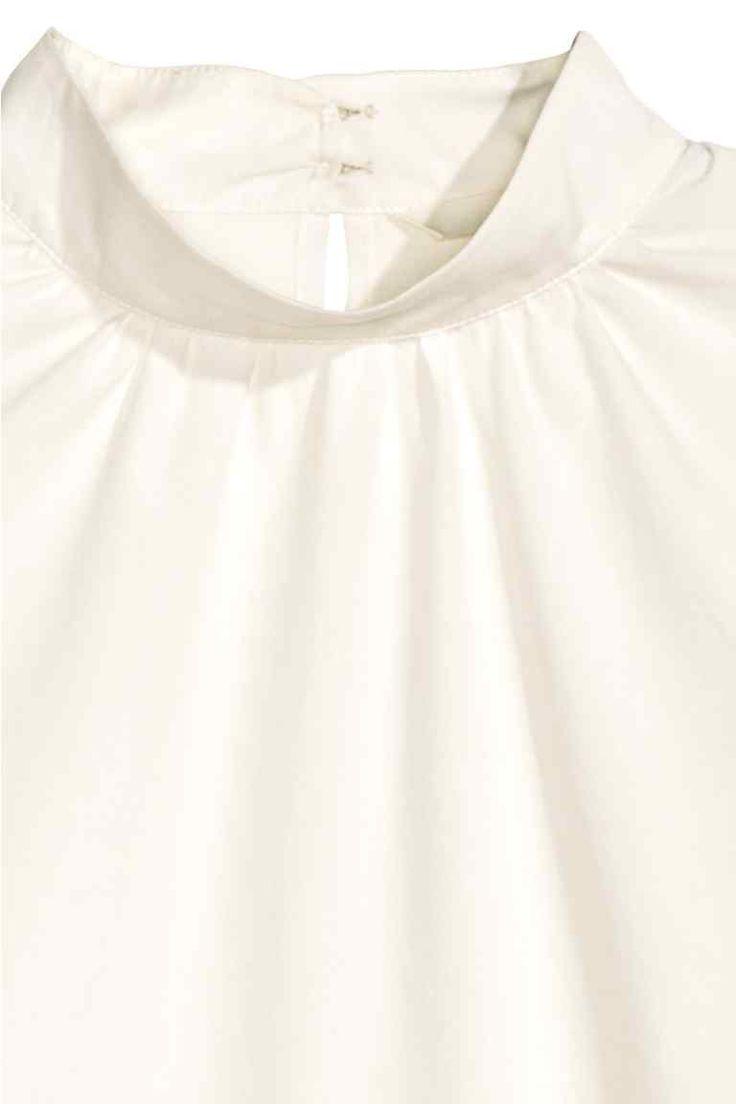 Хлопковая блузка: CONSCIOUS. Слегка расклешенная блузка из хлопковой ткани. На блузке воротник стойка, вырез сзади и застежка у ворота. Длинные присборенные рукава с широкими манжетами на пуговицах. Скругленный нижний край, по бокам разрезы. Хлопок в составе блузки - органический.