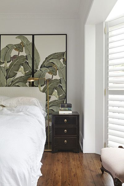 martinique wallpaper cut and glued to wooden panels to form bedhead. brass lamp. solid white bedhead blocks against the wallpaper