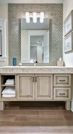 Grey penny tile wall as backsplash while framing mirror. Simple floors. Neutral colors
