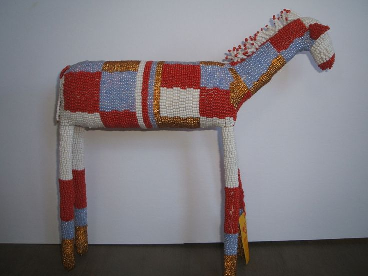 A unique beaded artwork made by disadvantaged people in the townships of Cape Town. Red, Lilac Gold and White, he stands 30cms high, and approx 30cms long. One only. www.homeworkhomewares.bigcartel.com