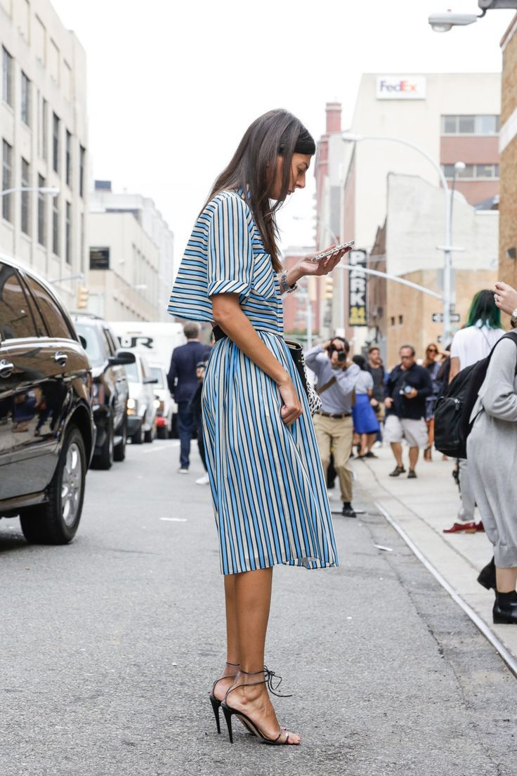 Giovanna Battaglia in a midi blue pin-striped dress, with lace-up silver sandals.