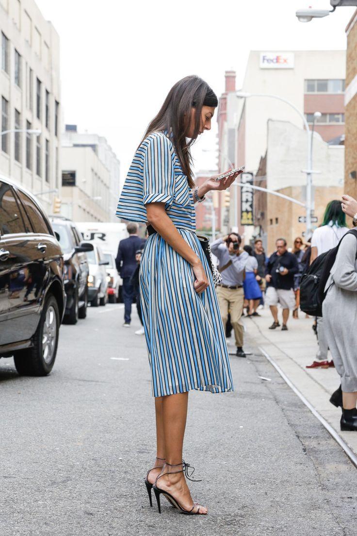 Giovanna Battaglia in a midi blue pin-striped dress, with lace-up silver sandals.