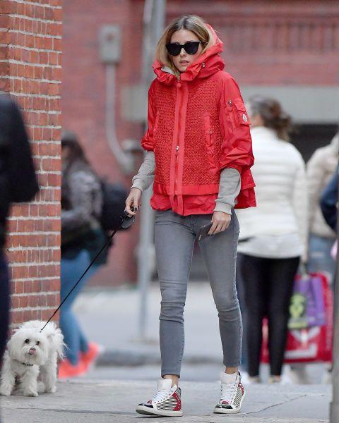 Olivia Palermo apuesta por el chubasquero en un favorecedor color rojo combinado con vaqueros grises y zapatillas.