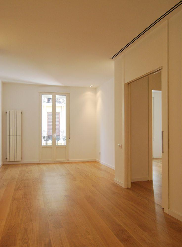 Salón de apartamento con suelo de parquet, rejillas lineales de aire acondicionado y radiadores verticales