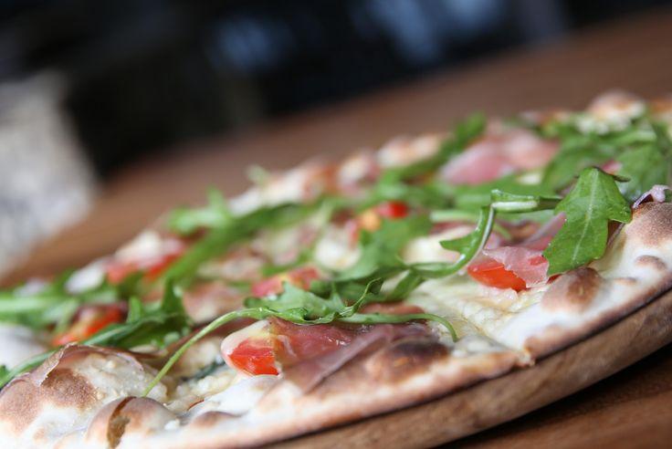 Bianca Di Prosciutto - Thin crust pizza with cured parma ham, fresh cherry tomato, rocket salad, mozarella, and extra virgin olive oil by Balboni Ristorante - Jakarta, Indonesia
