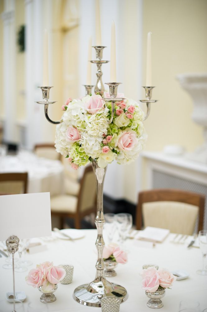 tall silver candelabra with a ball of soft ivory and pink summer flowers