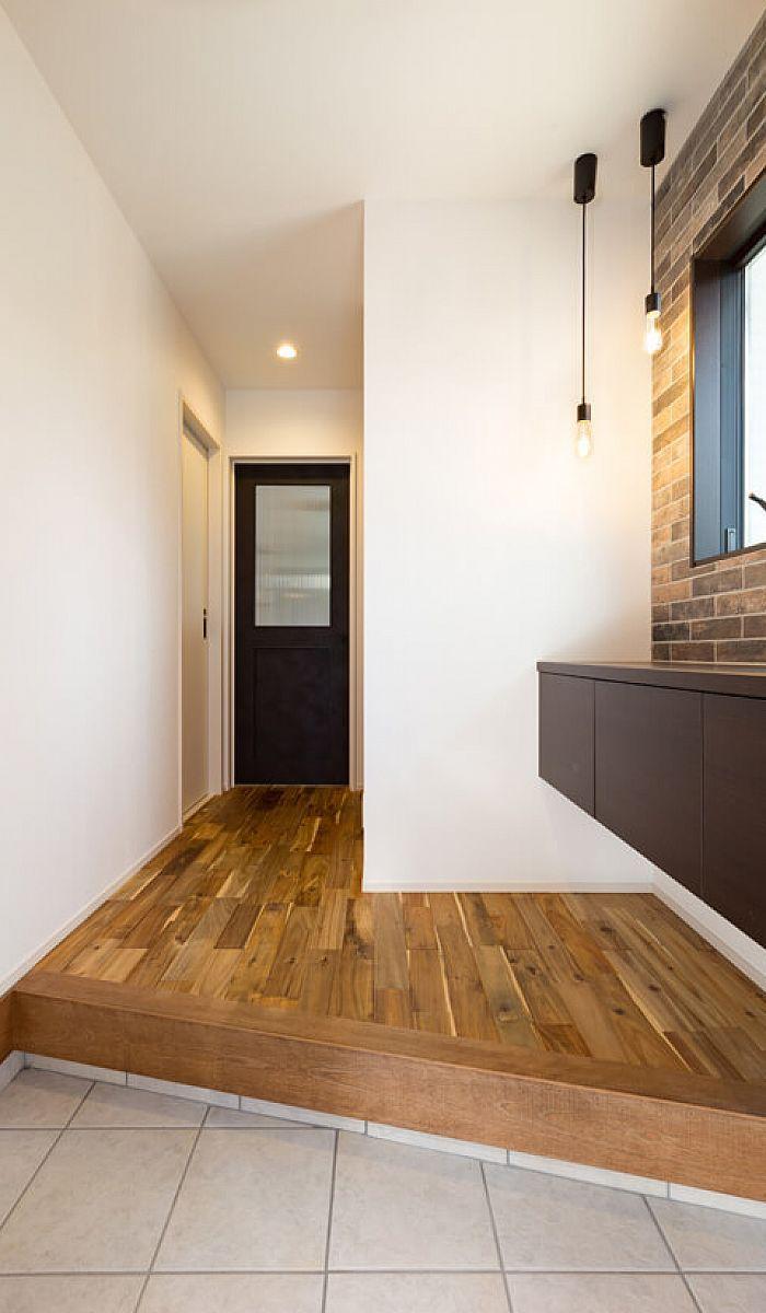 玄関はヴィンテージ感のあるタイルと武骨な電球型の照明でかっこいい