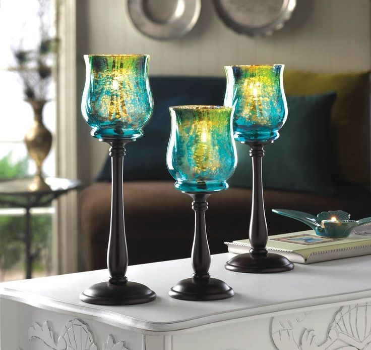 A trio of gorgeous glass mounted upon sleek spindles of black metal all with varying heights to create a stunning display. The iridescent blues and greens of the candle cups with sparkle with light up