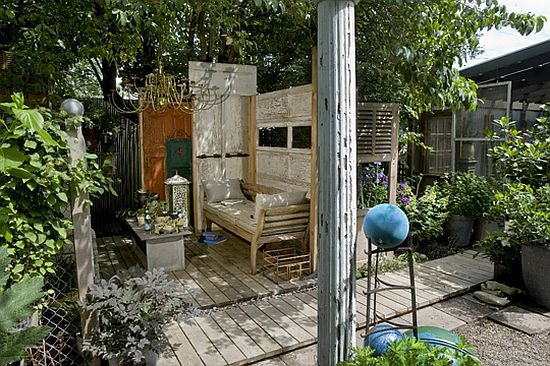 Outdoor room made of recycled materials including an old garage door, shutters, and corrugated metal!