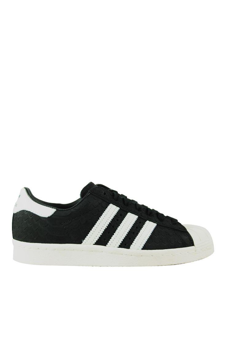 Γυναικεία Sneakers Adidas Originals Superstar 80S. Τα εμβληματικά sneakers της adidas από τα 80s έχουν επιστρέψει για τα καλά στις ζωές μας. Η χαρακτηριστική τους λαστιχένια μύτη τα διαχωρίζει από κάθε άλλο sneaker και ενώ ξεκίνησαν σαν παπούτσια του μπάσκετ, πλέον έχουν κατακτήσει το urban στυλ και λατρευτεί από μουσικούς, street style stars και bloggers ανά τον κόσμο. Αυτή η εκδοχή διαθέτει εφέ snakeskin ενώ είναι κατασκευασμένο από υλικά που κρατούν το πόδι δροσερό και άνετο.