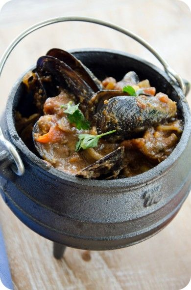 Spicy Seafood Potjie _ (mussels, kingklip (or other firm white fish), calamari tubes, and prawns) _ In a sensational sauce. Cooking stews in a three-legged cast iron pot or potjie over coals or open flame is a South African tradition.