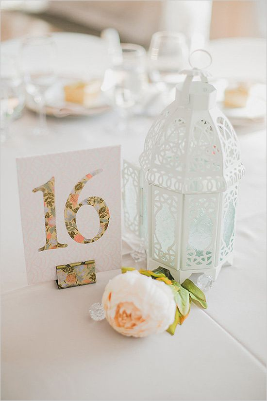 Floral table number and White lantern centerpiece. Photo by Rhythm Photography
