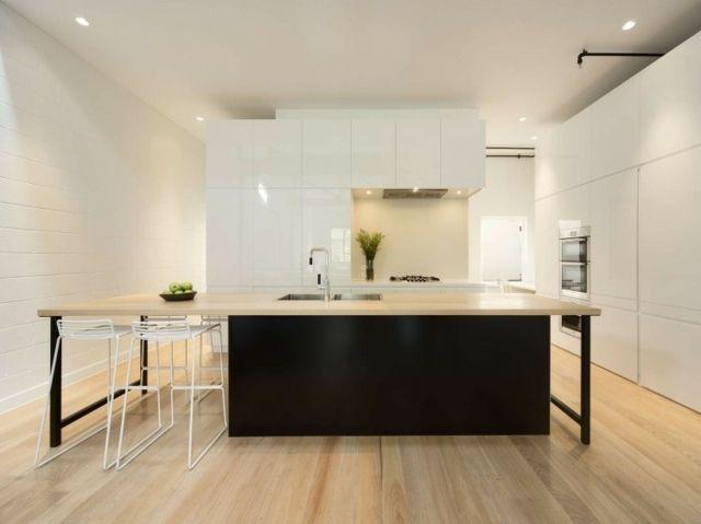 un îlot noir dans la cuisine blanche et élégante