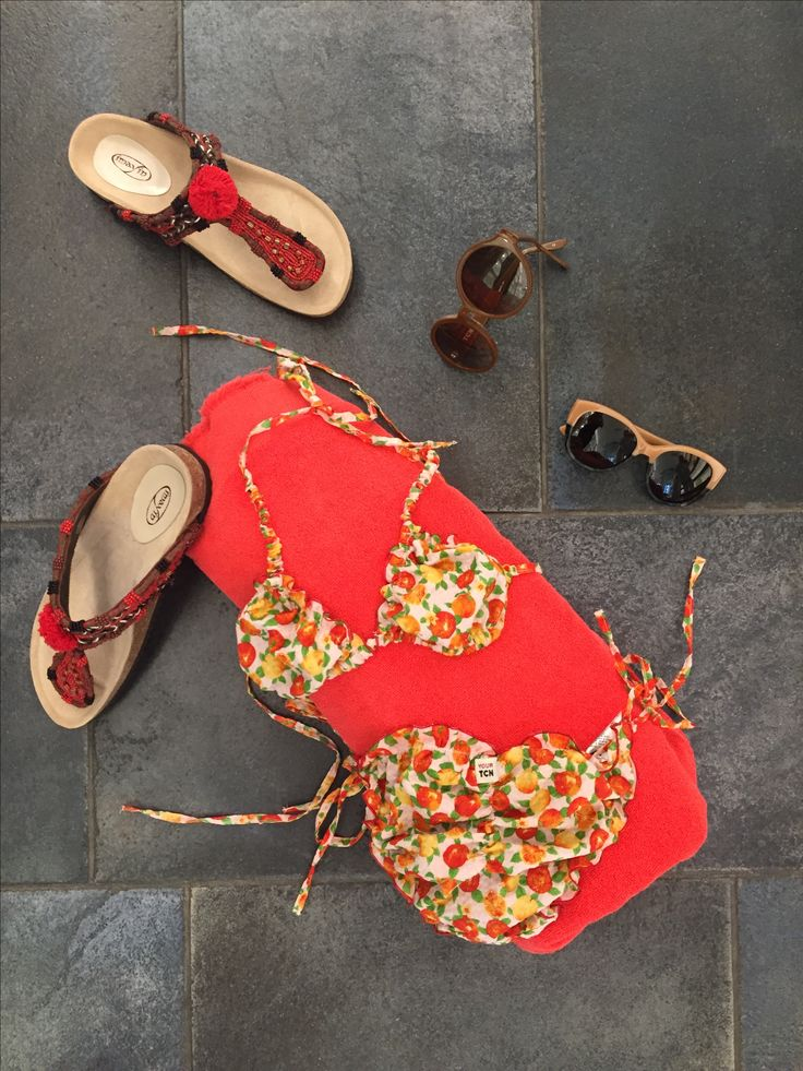 Bikini estilo halter de triángulo fruncido, con forro en canalé de algodón fácil de secar, estampado de flores. Sandalias adornadas con abalorios rojos y pompón, estilo étnico y suela de gran comodidad. Toalla de TCN tamaño playa, y gafas de la misma marca.