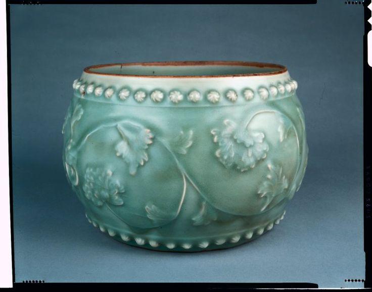ドラム形状の龍泉磁器の瓶。 jarファイルは、いくつかのクラックルと灰色がかった緑色の釉薬を持っています。 花の形をしたボスの二つのバンドの間に2つの成形マスクとリングハンドル付き外装の周りのリリーフで牡丹のスクロールは、あります。