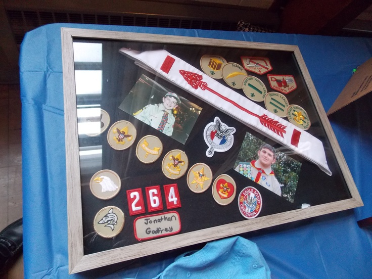 All ranks, patrols, NESA patch, Order of Arrow Sash (Brotherhood) in a picture frame. Use hot glue gun and sewing pins to attach patches, pictures, and sash to picture frame backing.
