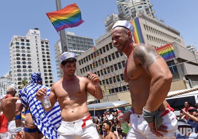 Gay men dance outside the American Embassy in the annual Gay Pride Parade in Tel Aviv, Israel, June 9, 2017. Tens of thousands of Israelis…