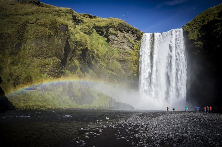 Group of people at foot of large waterfall, with rainbow