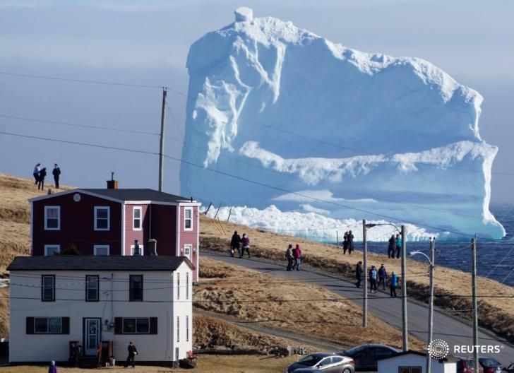 """Residents watch an iceberg as it passes """"Iceberg Alley"""" in Newfoundland, Canada"""