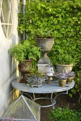 collection of small urns on a garden table