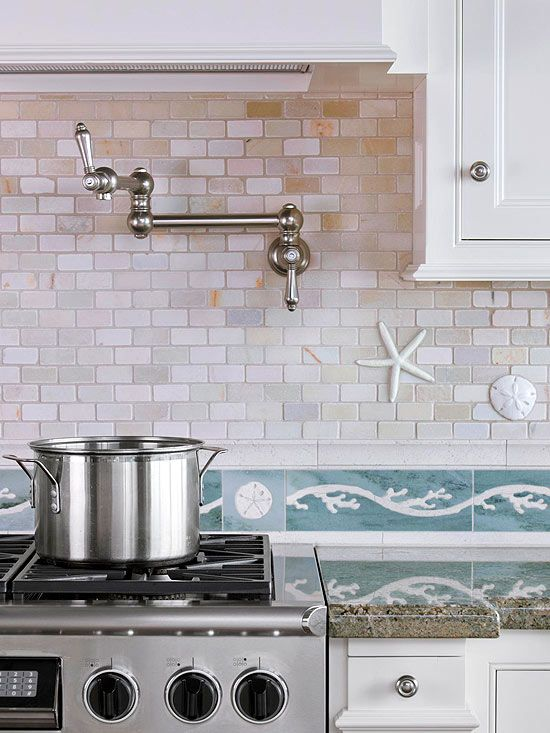 Even the backsplash was designed to complement the panoramic ocean views. Iridescent quartz subway tiles paired with a limestone sea motif embrace colors from the ocean beyond. A ceramic starfish and sand dollar bring dimensional beauty to the backsplash nearest to the range.