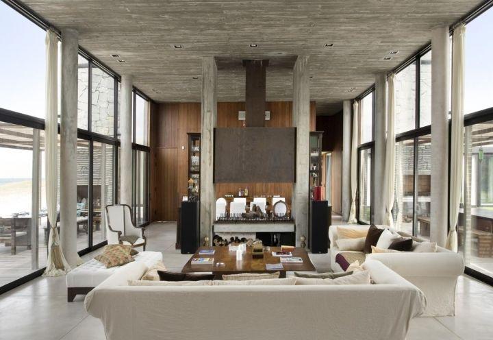 Una vista del living. Uno scenografico camino centrale definisce le funzioni: da un lato la sala e dall'altro la cucina, dove domina il calore del legno di provenienza locale