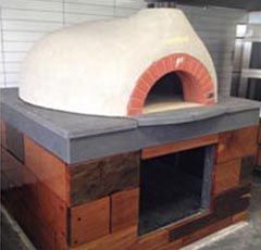 Vesuvio Wood Fired Oven – GR 120  Fire Chief – Camberwell, VIC  Built on a decorative wooden base and finished with a striking grey stone top, this wood fired oven is as beautiful as it is eye catching.