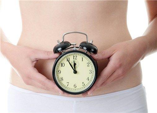 Una mujer se coloca un reloj en el vientre como símbolo de la regularidad del tránsito intestinal