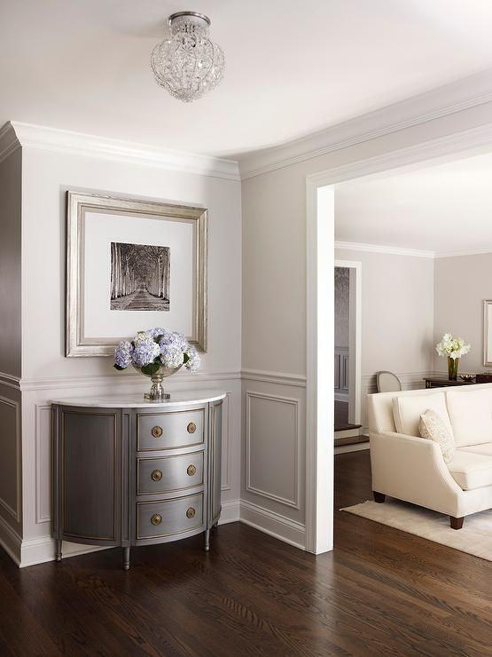Chic foyer features upper walls painted pale gray and lower walls clad in light gray wainscoting lined with a gray half moon console table with gold trim topped with white marble placed under a black and white photograph framed in a silver leaf frame.
