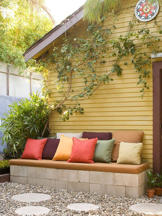 Furniture can be an expensive investment for backyards, but there are options for make-it-yourself benches, chairs, and tables. Here, low-cost concrete blocks, dry-stacked and covered with a foam pad, offer lots of seating in a high-traffic spot outside the home's back door./