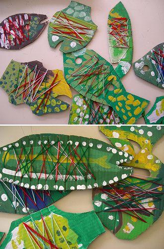 peixos de cartó decorats amb pintura i amb fils de colors