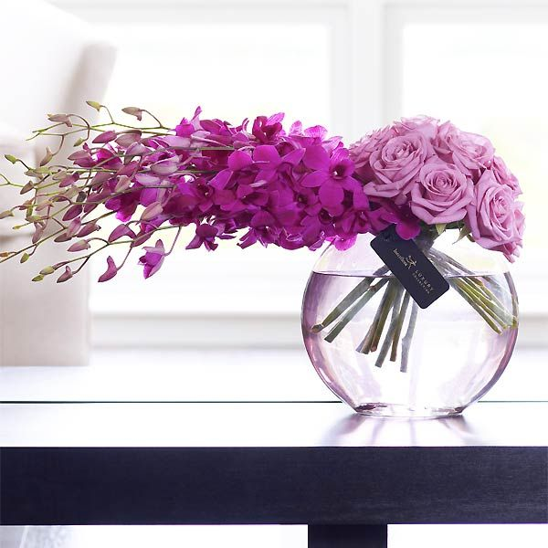 Lavender orchids and roses perched in clear vessel. Exquisite! #purpleflowers
