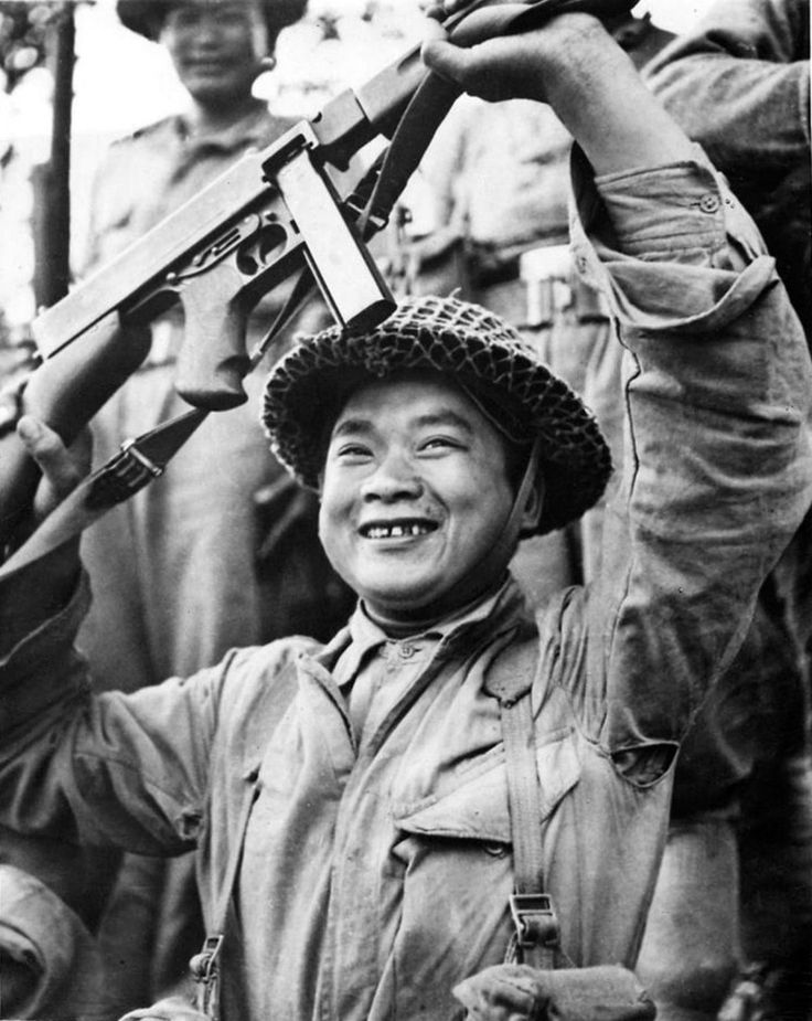 A cheerful Chinese soldier of the Chinese Expeditionary Force (CEF), under command of U.S. Army General Joseph Stilwell, waves his submachine gun following the successful crossing of the Tanai River in northern Burma during the Burma Campaign. The...