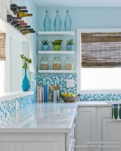 Stunning blue and gray tile create a colorful backsplash in this white kitchen with bead board paneled cabinet fronts. A touch of natural texture graces the windows in the form of bamboo shades. Did you notice the built-in wine rack above the pass-through window?