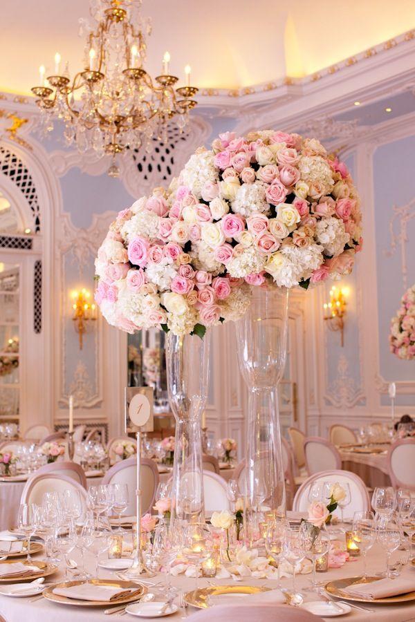 Decoracion de boda con topiarios de rosas sobre jarrones altos.