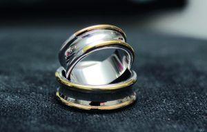 Argollas para hombre y mujer de forma convexa elaboradas en oro blanco, con bisel en oro amarillo y rosado. #RevistaNovias