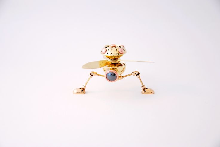 """Rotobot Mark 1 by Juhani Ananin. Steampunk miniature made from brass, bronze, copper and silver rivets with a cabochon cut hematite. 7 x 2,5 x 3 cm. Rotors 3,5 cm from the axle.  """"Time for a takeoff! """"  Photo: Hanna Silander"""