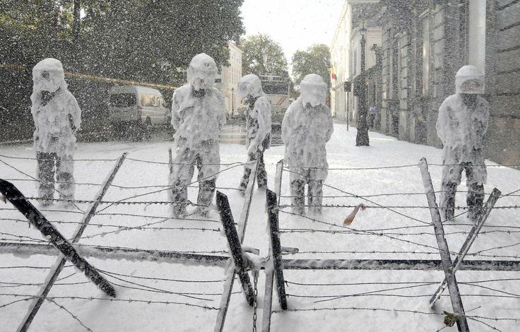 egy vicces kép az óév legjobb fotó válogatásaiból: Jobb munkakörülményekért tüntető tűzoltók oltó habbal terítették be a tünettés biztosítására kivezérelt rohamrendőröket Brüsszel központjában 2013. octóber 7-én. Fotó: Yves Herman/Reuters