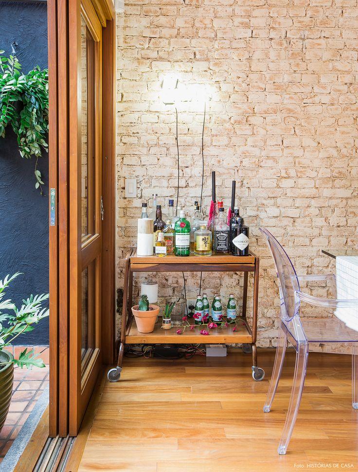 Carrinho de chá de madeira serve como bar nesse cantinho da sala de jantar.