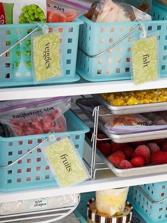 Un congélateur bien organisé à l'aide de paniers en plastiques de couleur bleu.